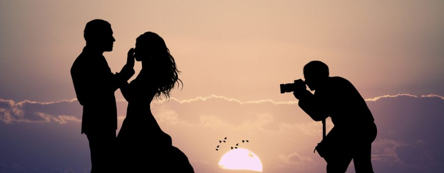 Photographer taking a photo of a couple at sunset